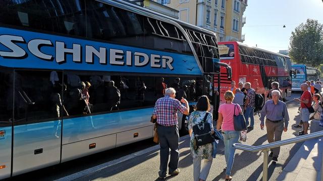 Passagiere warten vor Autobussen.