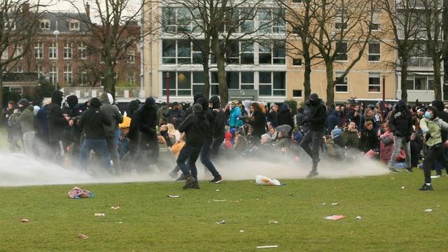 Die Polizei schiesst Wasserwerfer auf eine Gruppe von Menschen auf einer Wiese.