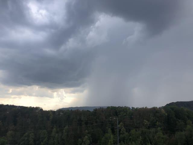 Aus einer Gewitterwolke ergiesst sich, wie ein grauer Vorhang, kräftiger Regen.