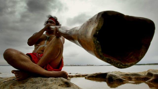 Mann spielt Didgeridoo.