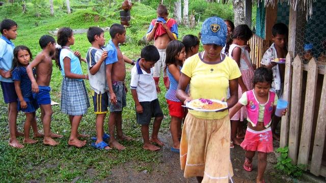 Eine junge Frau mit vollem Teller, hinter ihr eine Schlange Kinder vor der Essensausgabe.