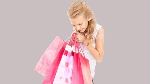 Mädchen schaut strahlend in verschiedene Einkaufstaschen in ihrer Hand.