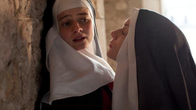 Die junge Nonne Suzanne wird von der Äbtissin an die Wand gedrückt. Suzanne wendet das Gesicht von ihr ab.