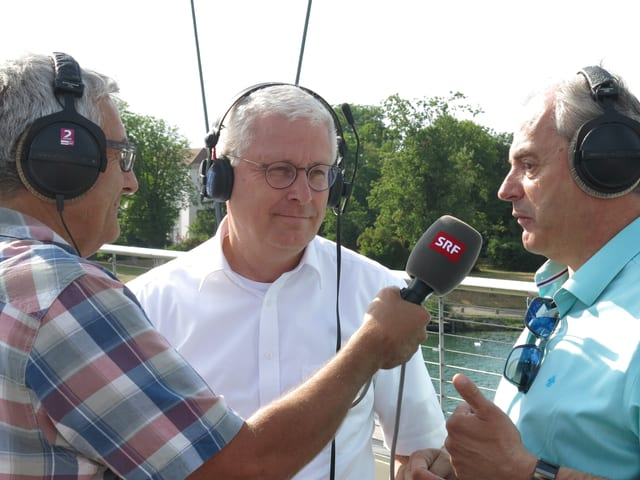 SRF-Redaktor Hansruedi Schär im Gespräch mit Wolfgang Dietz, Oberbürgermeister von Weil am Rhein und Jean-Marc Deichtmann, dem Maire von Huningue (v.l.n.r.)