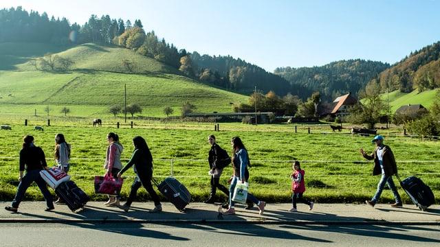Asylbewerber aus Syrien mit Rollkoffern laufen durch die Emmentaler Landschaft.
