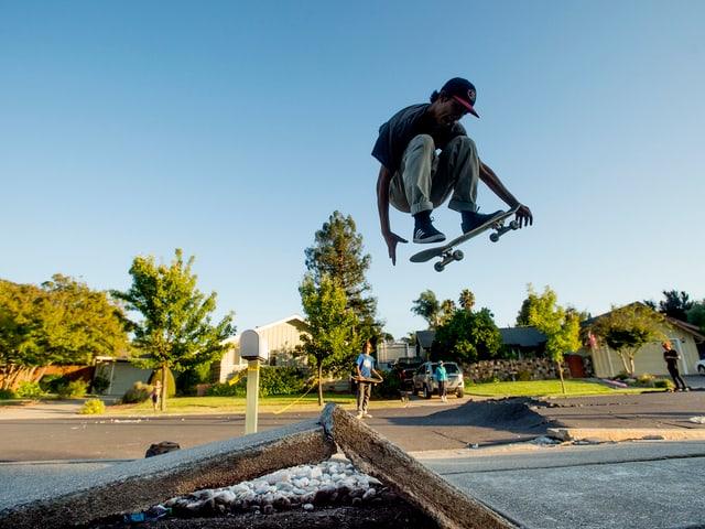 Ein Skater springt über eine Betonkante