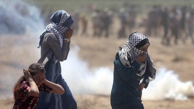 Trais dunnas che cuvieran cun faziels da chau palestinais e fim davostiers.
