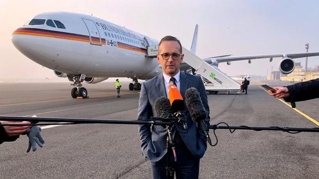 Heiko Maas auf einem Rollfeld vor Journalisten. Im Hintergrund steht sein Flugzeug.