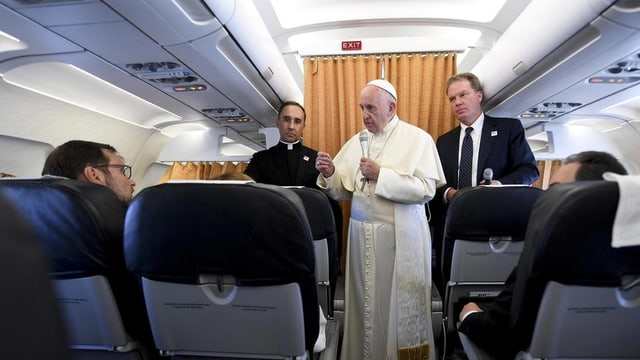 Purtret dal papa en in aviun durant ina conferenza da pressa.