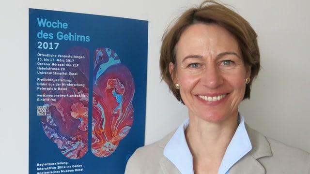 Portraitaufnahme von Catherine Alioth vor einem Veranstaltungsplakat der Woche des Gehirns