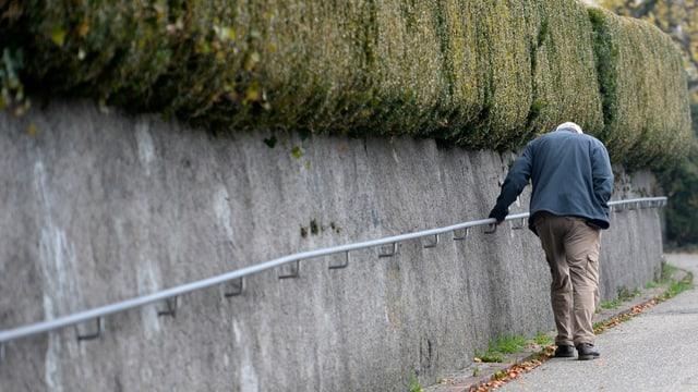 Ein älterer Herr stützt sich an einem Geländer.