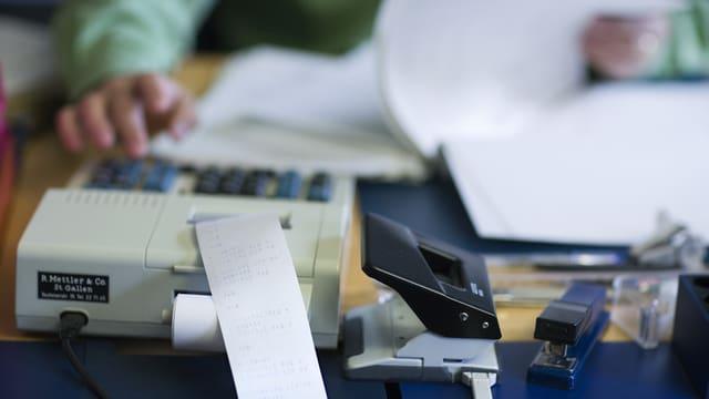 Eine Person benutzt einen Tischrechner und blättert zugleich in Unterlagen.