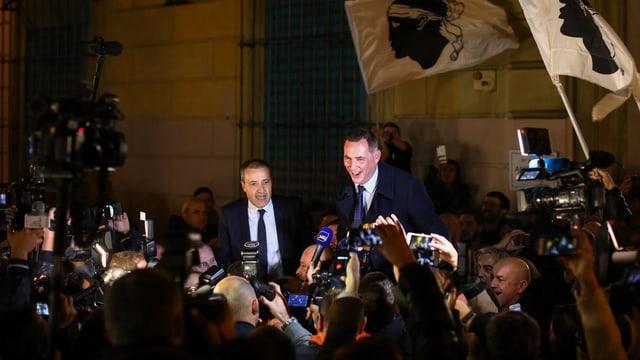 Zwei Männer im Blitzlichtgewitter von Fotografen, es wehen Korsika-Fahnen.