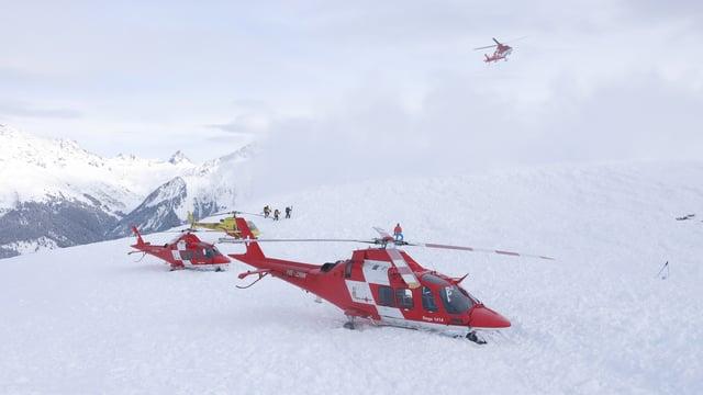 Zwei rot-weisse Rega-Helikopter auf einem Schneefeld.