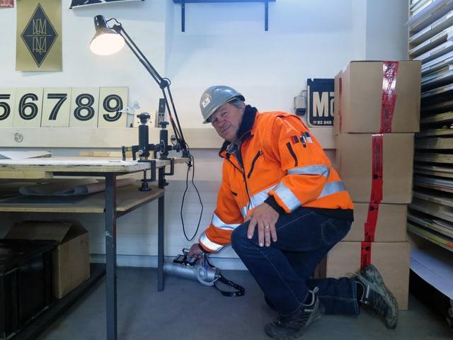 Ein Mann in oranger Leuchtjacke misst mit einem Gerät etwas in einem Arbeitsraum.