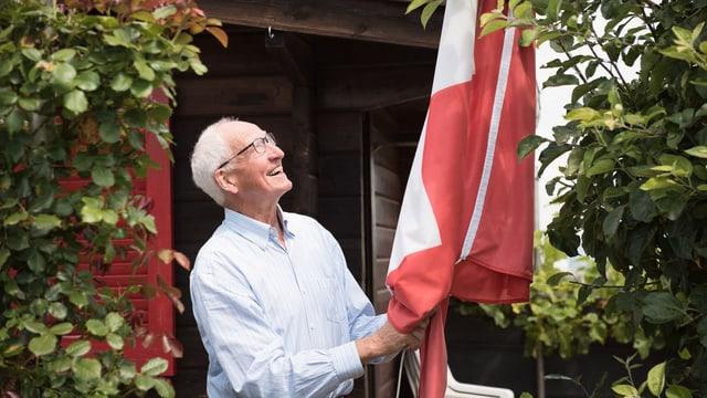 Ein älterer Herr blickt lachend auf eine Schweizerfahne.
