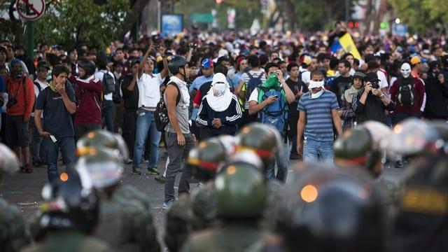 Eine Gruppe Oppositioneller stehen sich venezolanischer Regierungstruppen gegenüber.