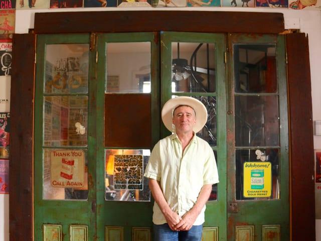 Ein Mann mit Hut steht vor einer grün gestrichenen Türe mit zahlreichen Fenstern.