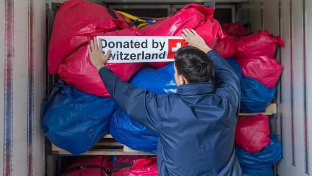 Ein Mann befestigt ein Banner an einer Hilfsgüterladung, darauf steht auf Englisch, von der Schweiz gespendet.