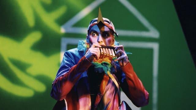 Ein Mann in einem buten Vogelkostüm spielt Panflöte.