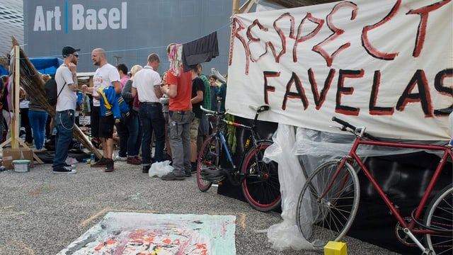 Vor der Messehalle mit dem Logo der Art stehen improvisierte Favelas.