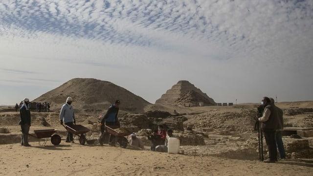 Arbeiter in der Wüste, im Hintergrund eine Stufenpyramide.