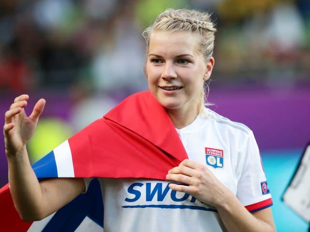 Hegerberg im Dress von Olympique Lyon mit der norwegischen Fahne auf der Schulter