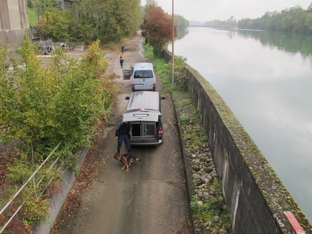 Am Aareufer stehen verschiedene Autos, ein Mann mit Polizeihund läuft vorbei.