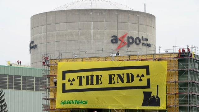 """Aussenaufnahme des AKW Beznau, im Vordergrund ein Transparent von Greenpeace mit der Aufschrift """"The End"""""""