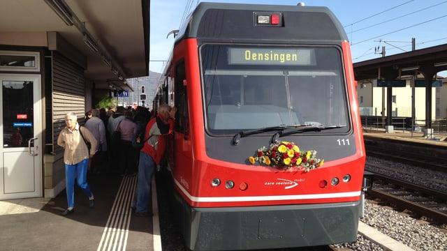 Rote Regionalzugskomposition an einem Bahnhof, Blumenschmuck an der Lokomotive. Zielbahnhof Oensingen wird auf Anzeigetafel gezeigt.