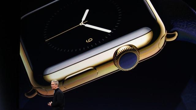Tim Cook stellt die Apple Watch vor. Sie ist hinter ihm gross auf einem Bildschirm.