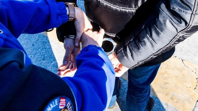 Polizist legt einer Person Handschellen an.