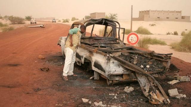 Ein ausgebrannter Pritschewagen am Strassenrand in Mali.