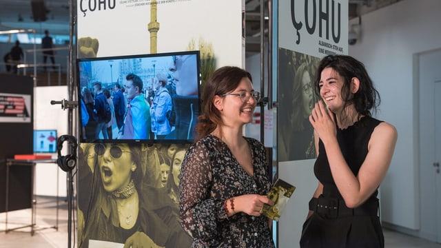 """Zwei junge Frauen stehen lachend vor einer Plakatwand mit dre Aufschrift """"çohu"""""""