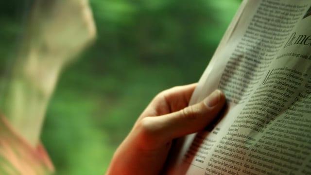 Eine Hand, die eine Zeitung hält.