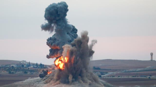 Eine Explosion mit Feuerball schleudert Erde in die Luft, im Hintergrund ist eine Stadt zu sehen.
