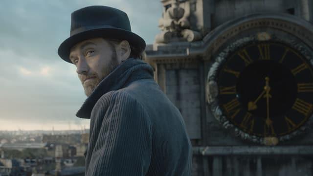 Mann mit Hut, hinten eine Kirchenuhr.
