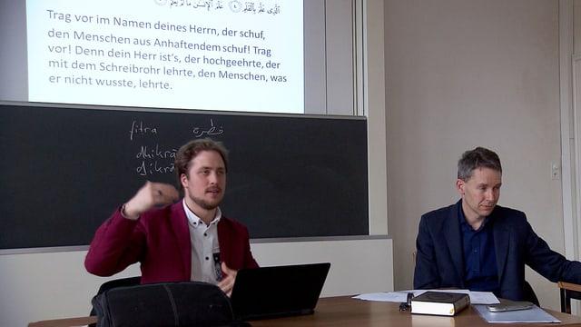 Vor einer Wandtafel sitzen zwei Männer, einer erklärt, im Hintergrund ist ein Ausschnitt aus einem Korantext an die Wand projiziert..