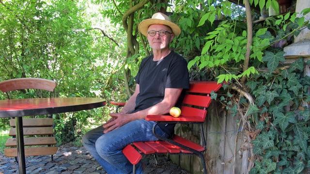 Leopold Huber sitzt auf einer roten Bank in seinem Garten.