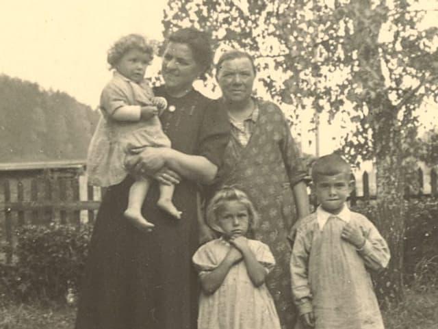Drei Kinder mit Tante und Grossmutter auf Feldweg.