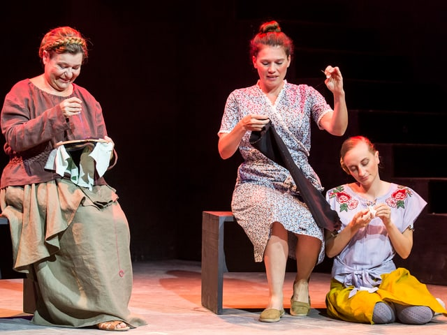 Drei Frauen sticken bei der Aufführung auf der Bühne.