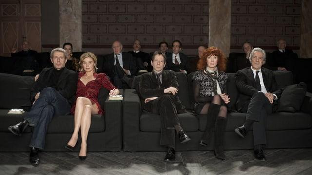 Eine Menschengruppe sitzt auf schwarzen Sofas und schaut direkt in die Kamera.