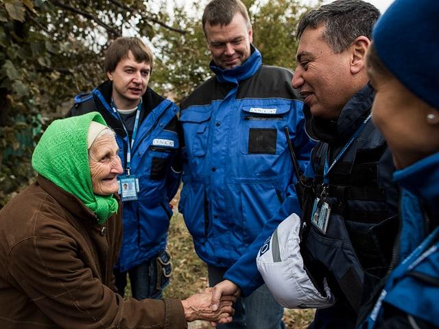 Eine alte Frau mit grünem Kopftuch schüttelt den OSZE-Beobachtern die Hand, sie lächelt.