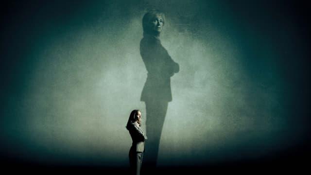 Eine Frau steht in einem dunkeln Raum. Ihr Schatten fällt dramatisch auf die Wand. Auf der Wand ist in dem Schatten wieder ein Frauengesicht zu erkennen.