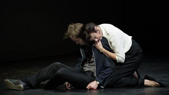 Schauspieler auf der Bühne: Ein Mann sitzt mit gesenktem Kopf am Boden, eine Frau umarmt ihn weinend.
