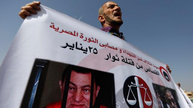 Ein Angehöriger einer getöteten Demonstrantin hält ein Banner hoch