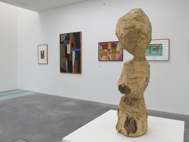 Vorne eine geschnitzte Holzfigur, hinten Bilder an der Wand.