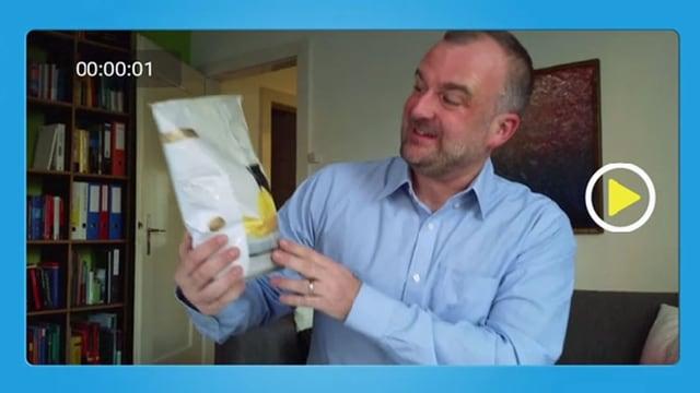 Mann betrachtet Chips-Verpackung.