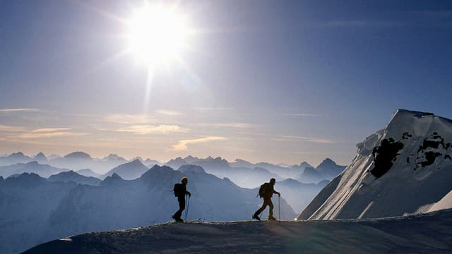 Zwei Bergsteiger auf einem Grat mit Alpenpanorama.