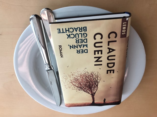 Der Roman «Der Mann, der Glück brachte» liegt auf einem weissen Teller. Messer und Gabel auf der rechten Seite sind neben das Buch gelegt.